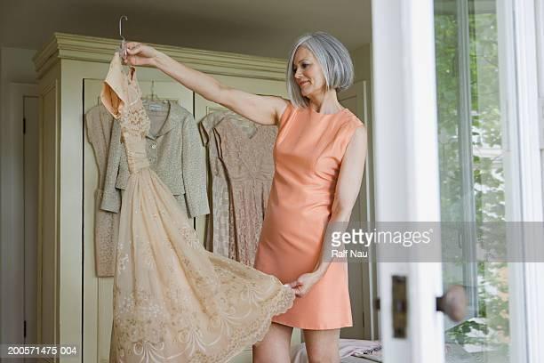 Mature woman looking at dress, smiling