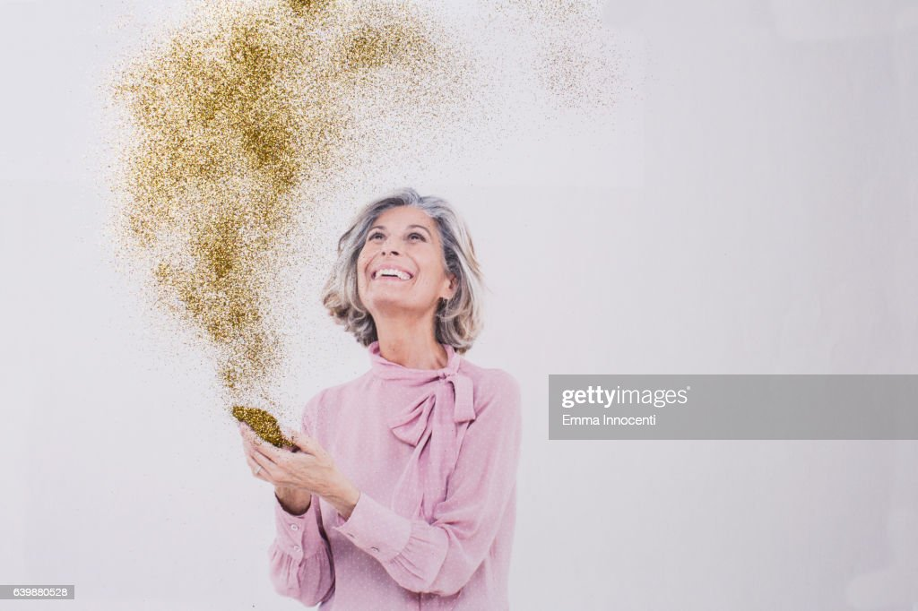 Mature woman looking at gold dust from phone : Stock Photo