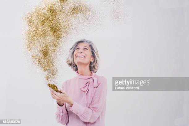 mature woman looking at gold dust from phone - alleen één seniore vrouw stockfoto's en -beelden