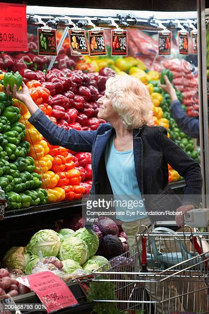 Mature woman looking at green bell peppers in supermarket