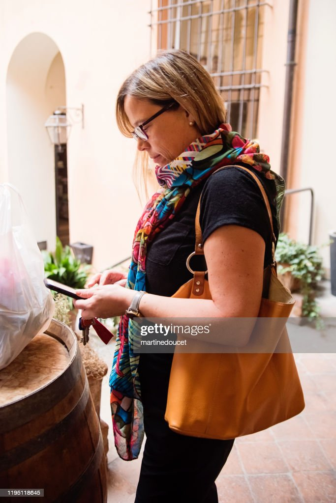 Mature woman looking at her phone outdoors. : Stock Photo