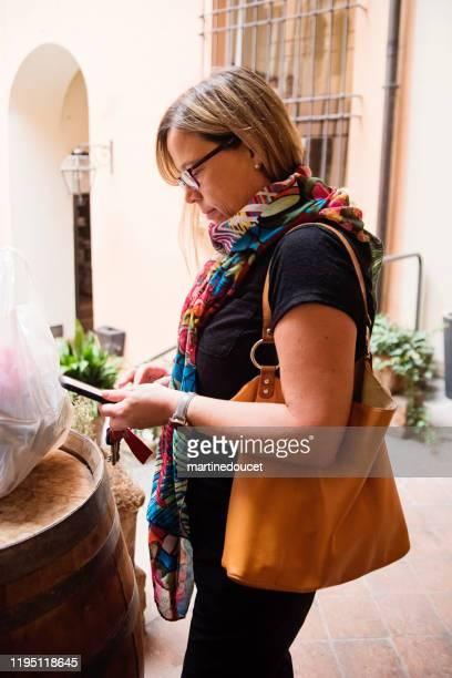 """mujer madura mirando su teléfono al aire libre. - """"martine doucet"""" or martinedoucet fotografías e imágenes de stock"""
