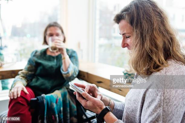 Mature woman looking at mobile phone in a local coffee shop.