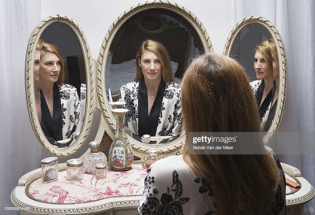 Mature woman looking at reflection in bedside mirror : Stock Photo