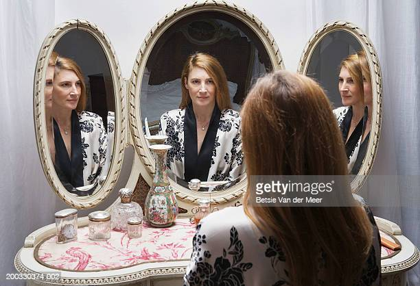 mature woman looking at reflection in bedside mirror - vanity stock pictures, royalty-free photos & images