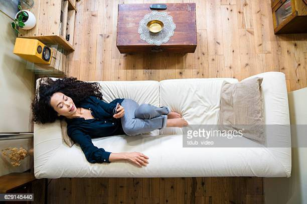 mature woman looking at smartphone while lying on a sofa - tdub_video stock pictures, royalty-free photos & images