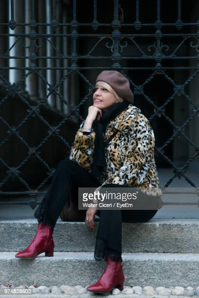 mature woman looking away while sitting on steps - walter ciceri foto e immagini stock