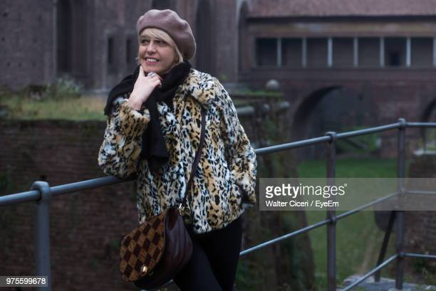 Mature Woman Looking Away While Standing By Railing