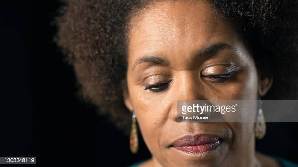 mature woman looking down - sadness stock pictures, royalty-free photos & images