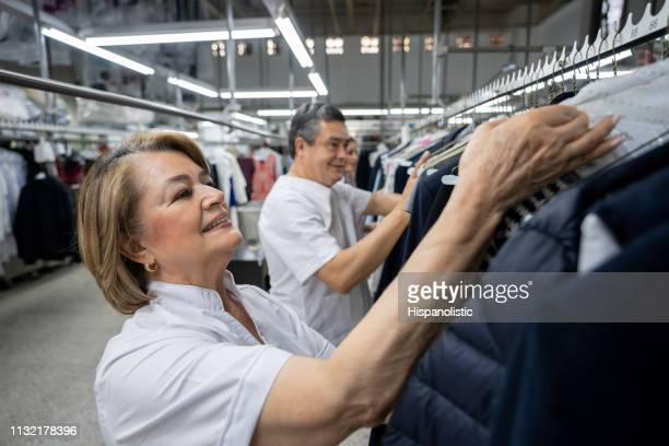 mature woman looking for a clothing on conveyor belt at a laundry service - dry cleaned stock pictures, royalty-free photos & images