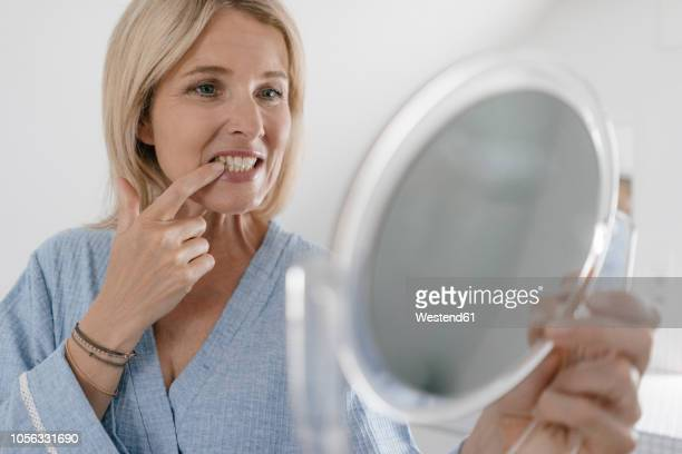 mature woman looking in beauty mirror in bathroom checking her teeth - teeth stock pictures, royalty-free photos & images