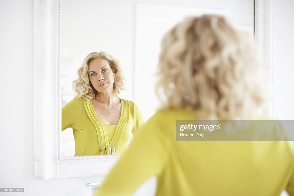 Mature woman looking in mirror : Stock Photo