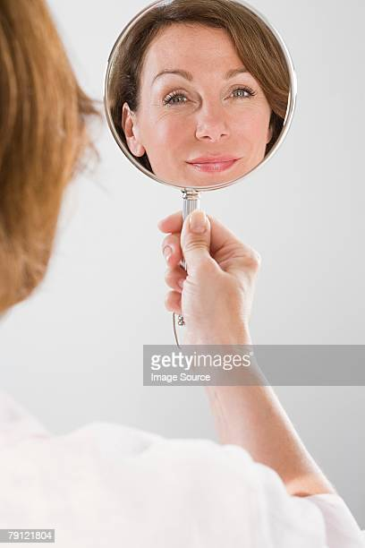 mature woman looking in mirror - hand mirror stock pictures, royalty-free photos & images