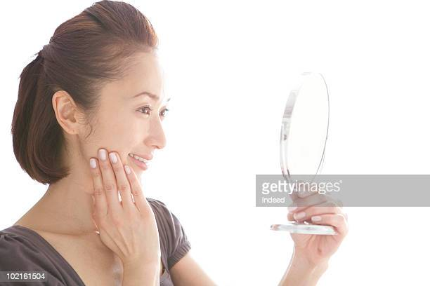 Mature woman looking in mirror, touching cheek
