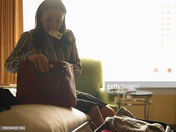 mature woman looking in purse in hotel room, card key in mouth - open blouse stock photos and pictures