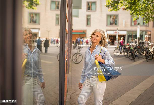 Mature woman looking in the window of a retail store