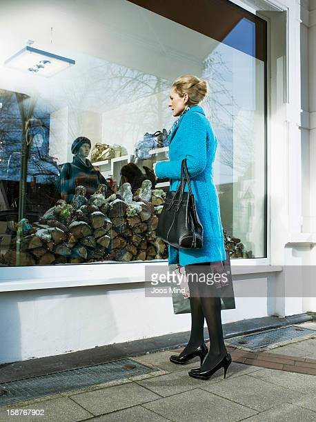 mature woman looking into clothing shop window