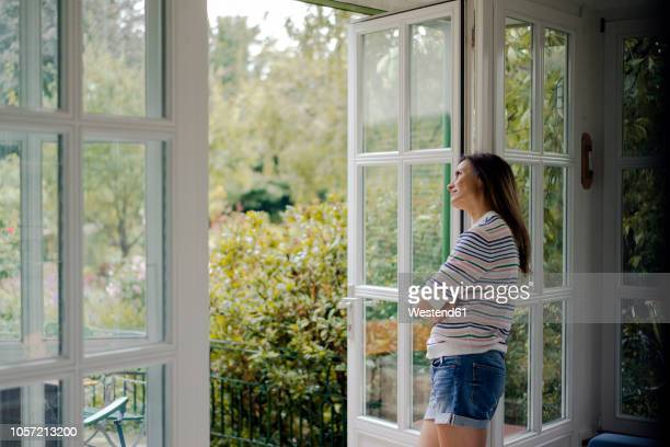 mature woman looking out of terrace door at home - patio doors stock pictures, royalty-free photos & images