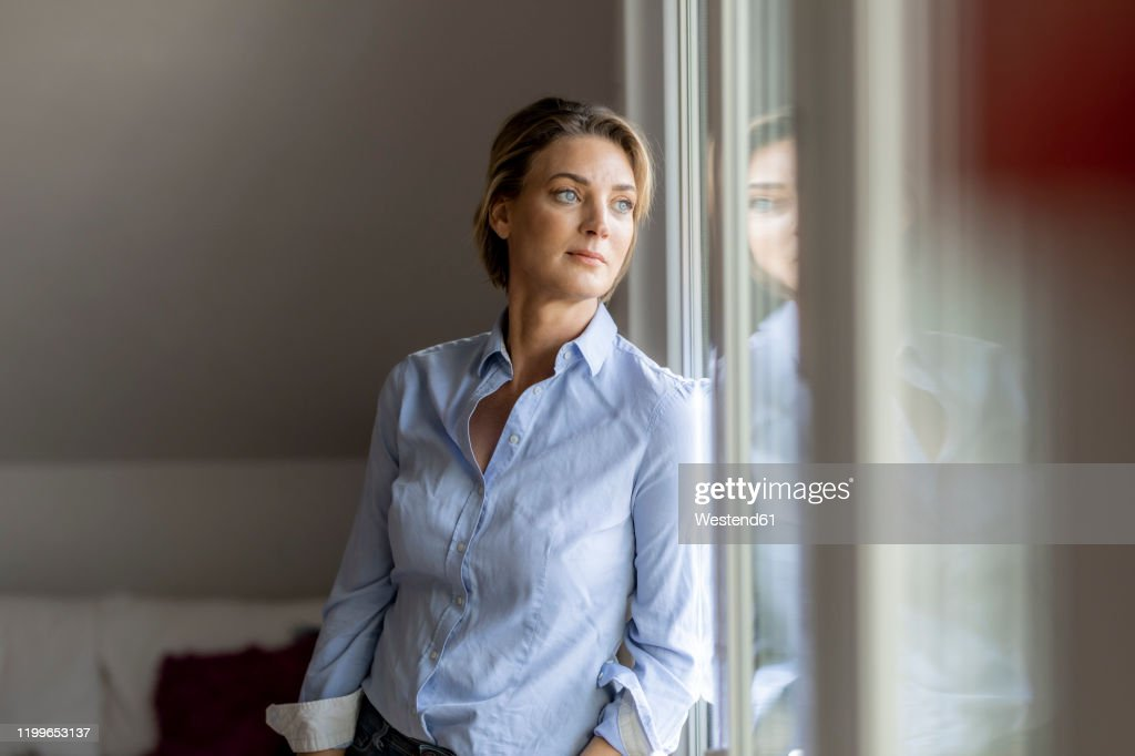 Mature woman looking out of the window at home : Stockfoto