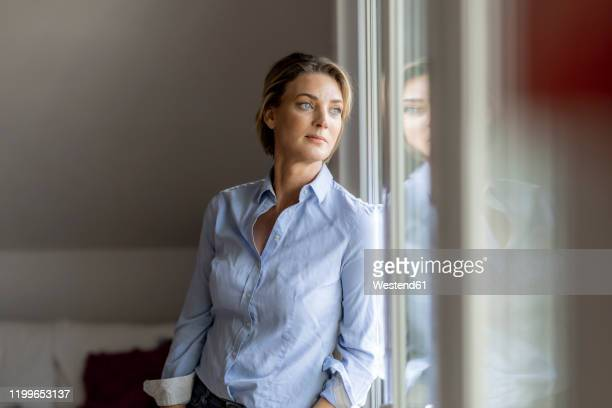 mature woman looking out of the window at home - verdriet stockfoto's en -beelden