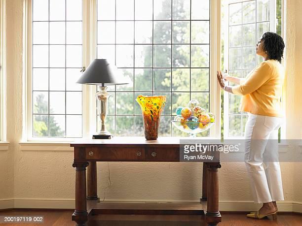 Mujer madura mirando por la ventana abierta en la sala de estar