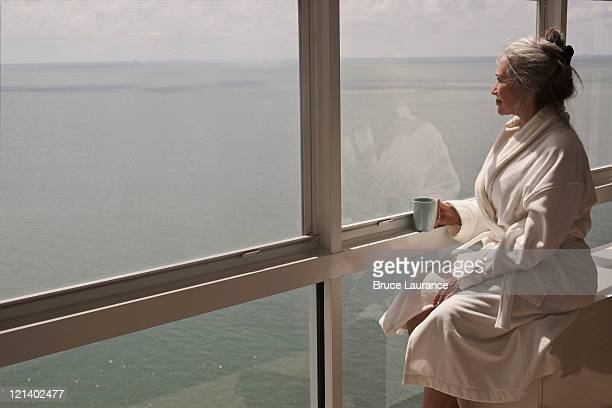 Mature woman looking out window