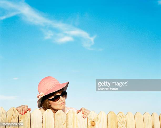Mature woman looking over fence