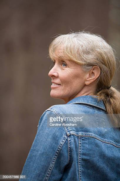 Mature woman looking over shoulder, smiling, rear view