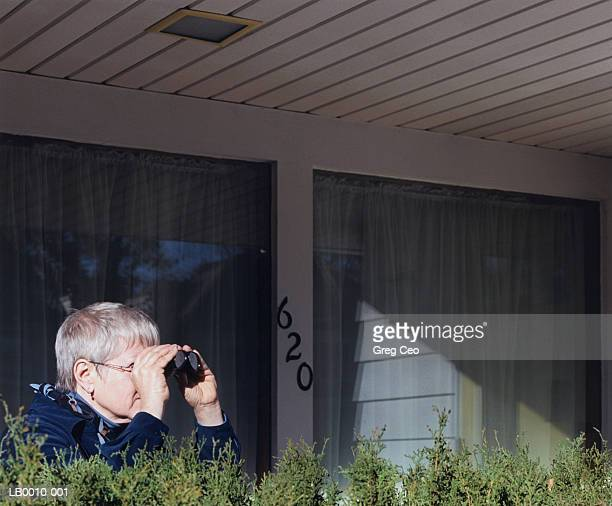 Mature woman looking through binoculars outside house