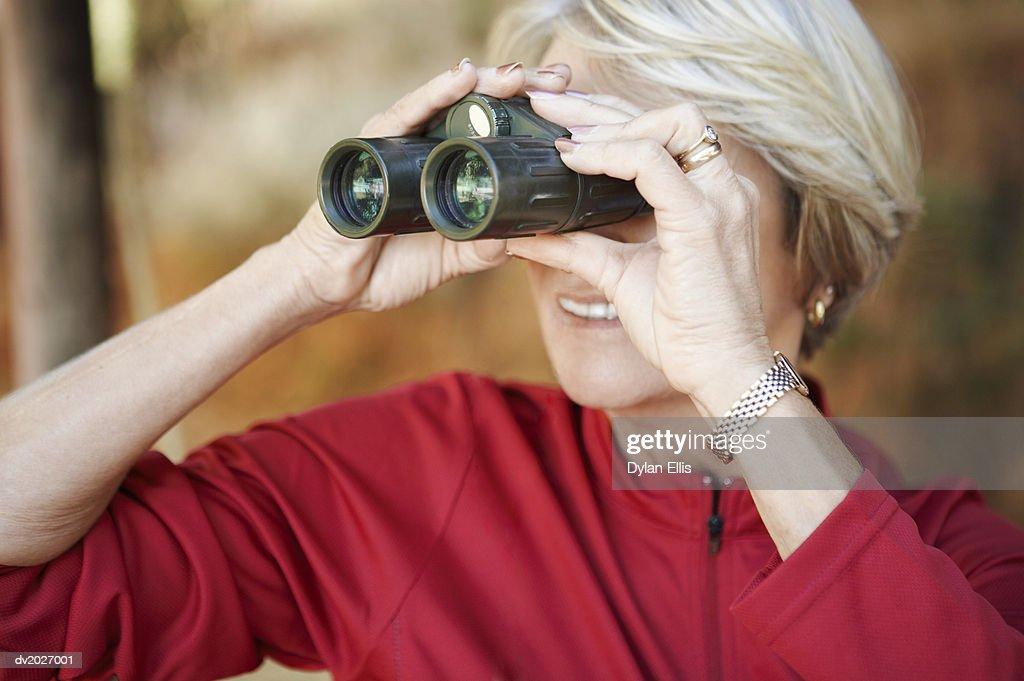 Mature Woman Looking Through Binoculars : Stock Photo