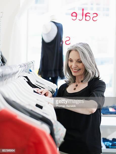 Mature woman looking through clothing rack