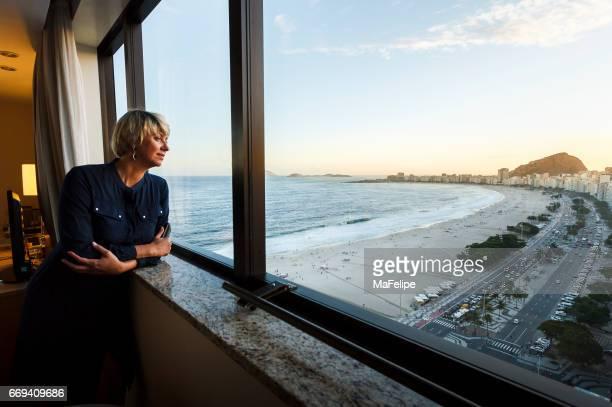 reife frau blick durch fenster aus ihrem hotelzimmer - copacabana rio de janeiro stock-fotos und bilder