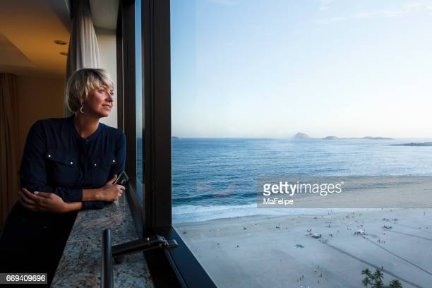 Mature woman looking through window from her hotel room