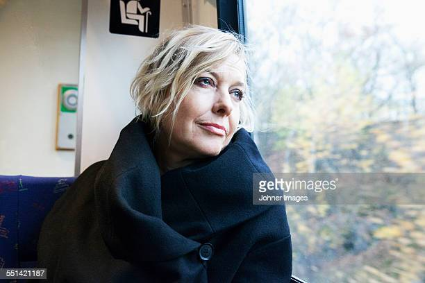 Mature woman looking through window in train
