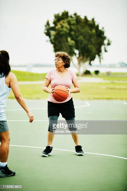 mature woman looking to make pass during basketball game on outdoor court - zakelijke kleding stock pictures, royalty-free photos & images