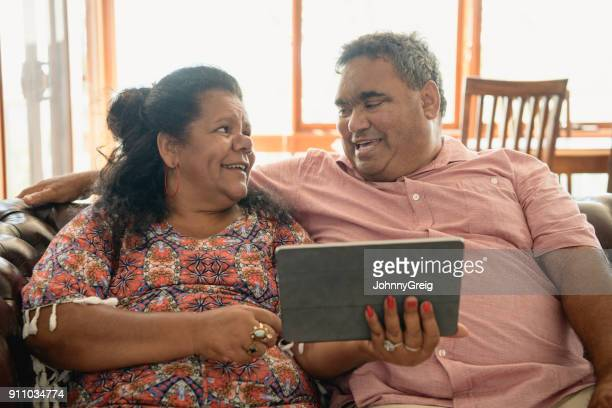 Mature woman looking towards man and holding digital tablet
