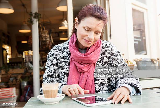 mature woman looks at ipad sitting outside cafe.