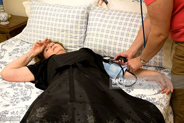 mature woman lying bed. fainted. blood pressure gauge. healthcare. medical. - fainting stock pictures, royalty-free photos & images