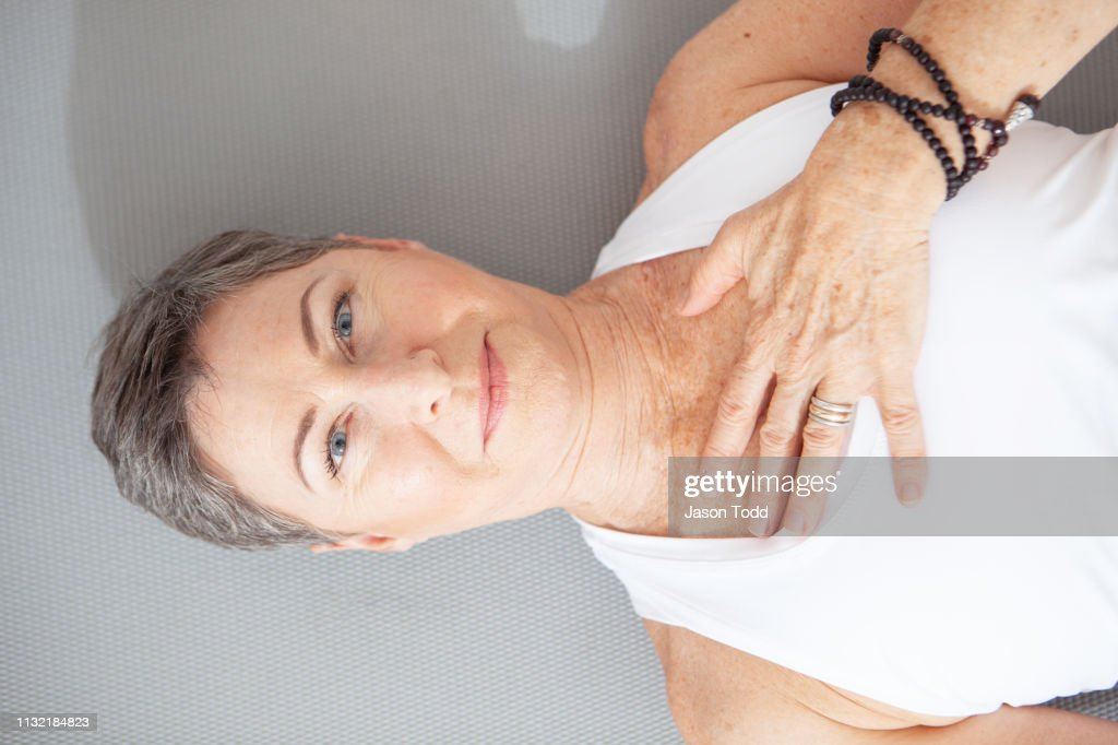 mature woman lying down on her back with eyes open and hand on chest : Stock Photo