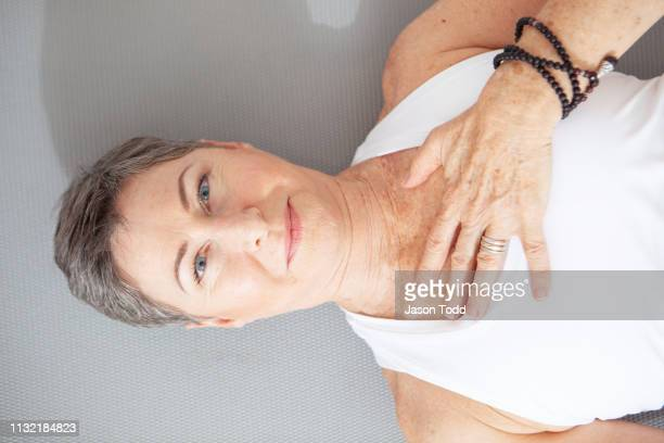 mature woman lying down on her back with eyes open and hand on chest