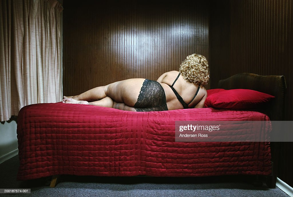 Mature woman lying on bed, rear view : Foto de stock