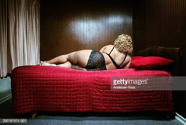 mature woman lying on bed, rear view - chubby stock photos and pictures