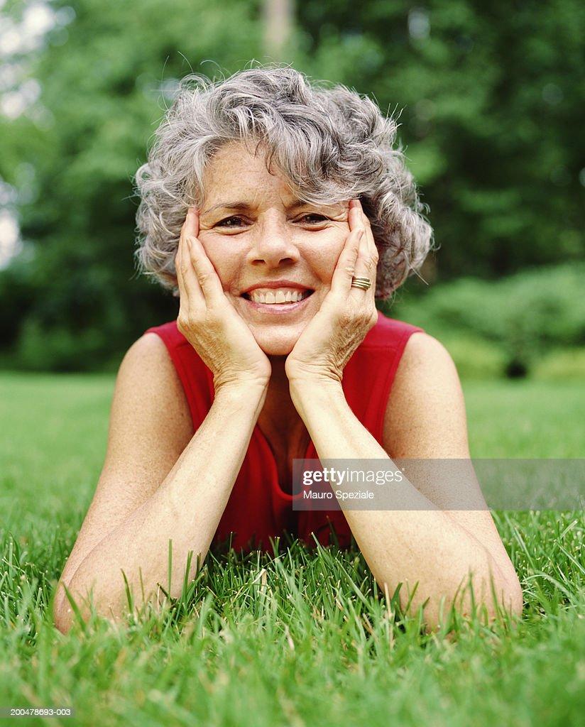 Brunette Woman Resting Outside On Grass Stock Photo