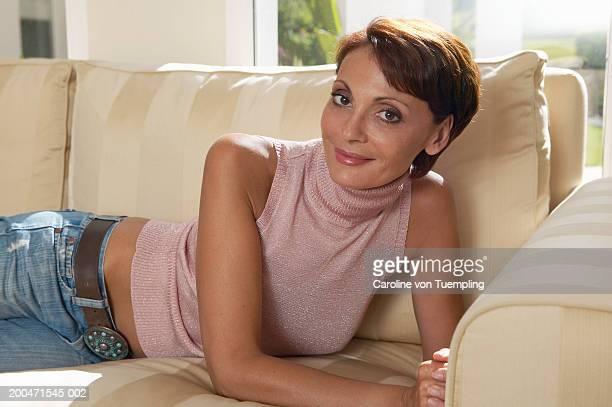 mature woman lying on sofa, portrait - caroline roux photos photos et images de collection