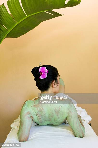 mature woman lying on table at spa, mud on back, rear view - schiff stock photos and pictures