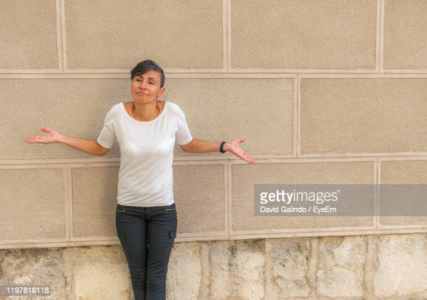 mature woman making face while standing against wall - caricature stock pictures, royalty-free photos & images
