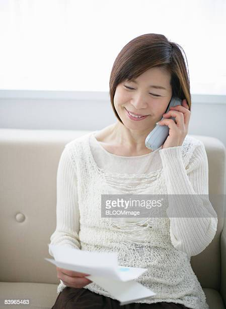 Mature woman making phone call, reading letter
