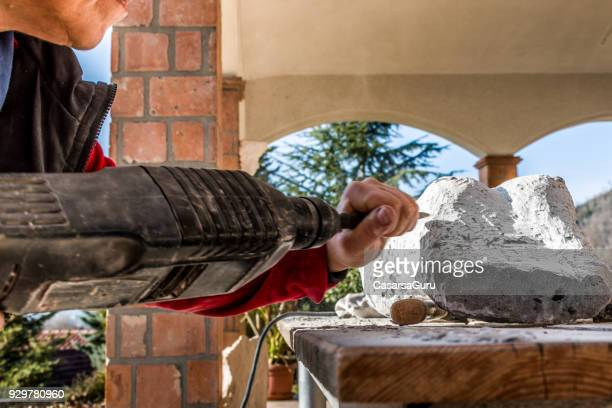 Mature Woman Making Sculpture From Repen Stone