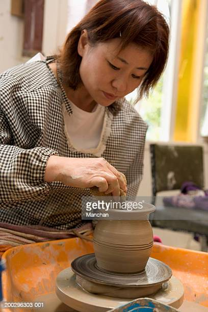 Mature woman making vase on pottery wheel, close-up