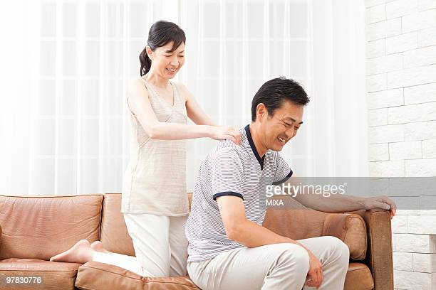 mature woman massaging mature man's shoulder - body massage japan stock pictures, royalty-free photos & images